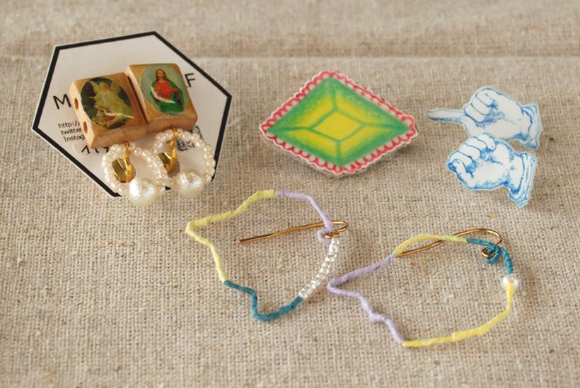 *ヴィンテージのビーズを使ったイヤリング(写真左)や、手漉き和紙のピアス(写真手前)、手書きのイラストのアクセサリー(写真奥)なども制作している